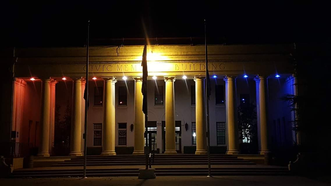 red, white and blue lights shine on the Willows Memorial Hall